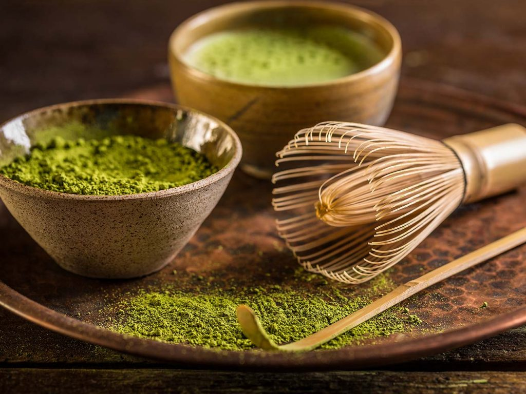 Ceremonial matcha tools including a brush, small pot of matcha power and wooden stiring stick