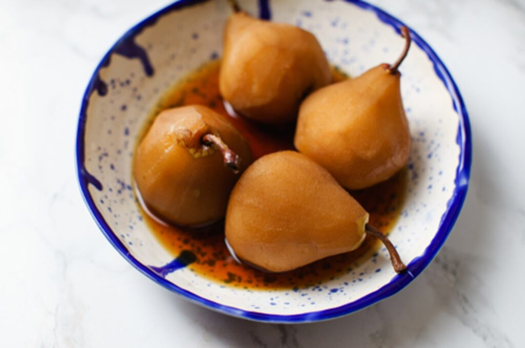 Four Poached pears in spiced tea in a ceramic blue bowl
