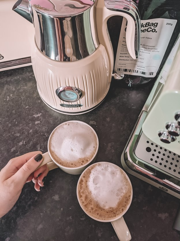 Mollie Quirks hand resting on two mugs of cappuccino made with our Retro Pump Espresso Coffee Machine resting on a black marble countertop