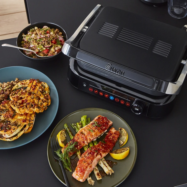 Photograph of the Swan Stealth Smart Grill next to a plate of grilled cauliflower, couscous and grilled pork on a bed of asparagus