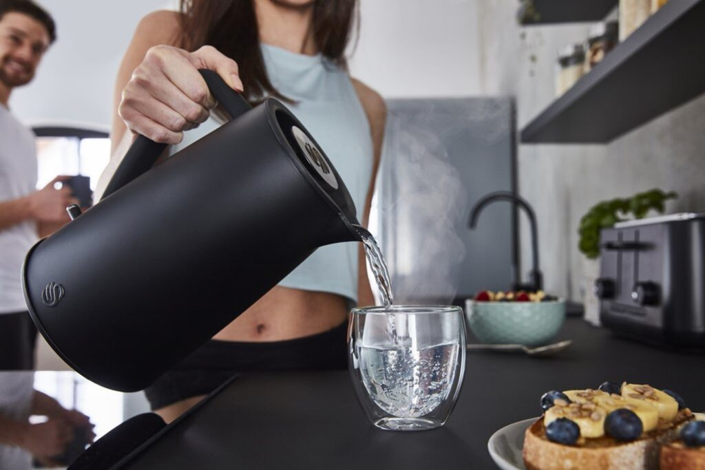 Photograph of woman pouring boiling water from the Swan Stealth Kettle
