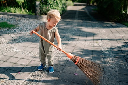 Photograph of young child cleaning a stone driveway with a wooden brush