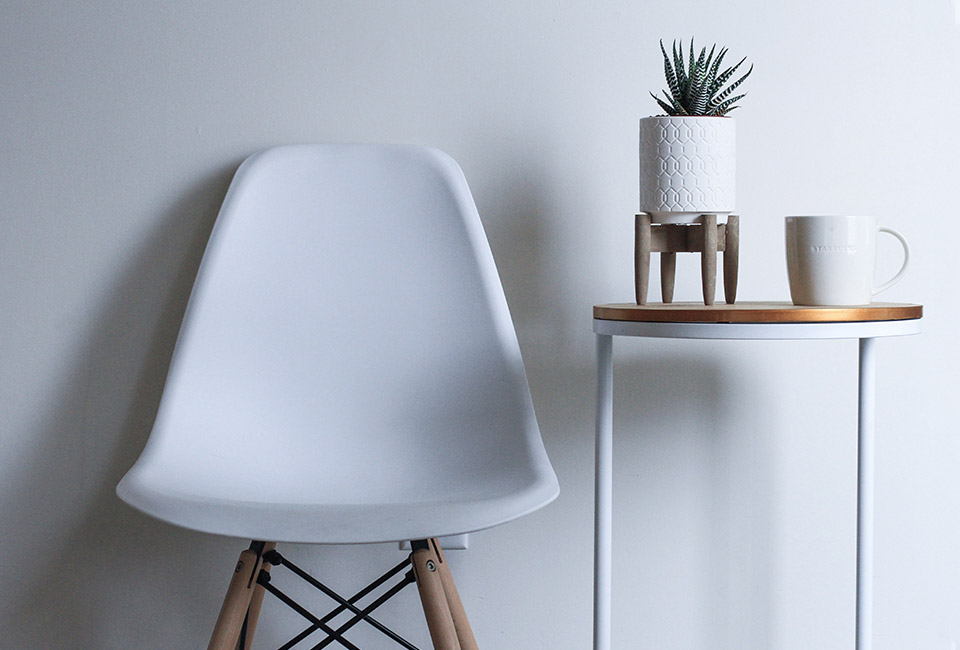 White chair next to a white stand table with white potted plant and white mug resting on top
