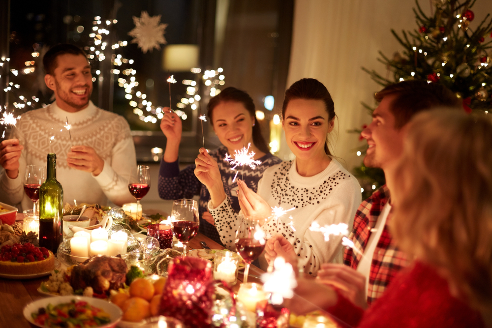 Photograph of a family at christmas time sat at the table holding sparklers