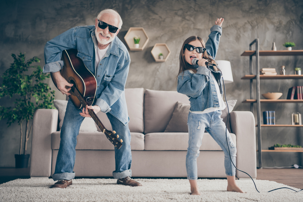 Photograph of a grand father and grand daughter playing a guitar and singing