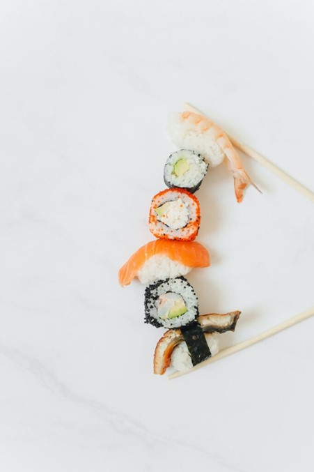 A line of sushi rolls with raw fish against a white background with two wooden chopsticks nearby